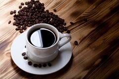 Granos de café y café en la taza blanca en la tabla de madera selectivo Foto de archivo libre de regalías