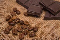Granos de café y chocolate oscuro en una servilleta de lino imagenes de archivo