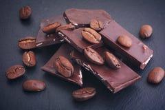 Granos de café y chocolate oscuro roto en fondo negro imagen de archivo