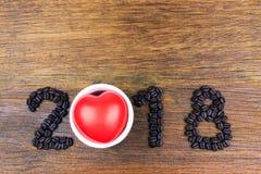 granos 2018 de café y corazón rojo en la madera Imagen de archivo