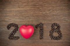 granos 2018 de café y corazón rojo en la madera Fotos de archivo