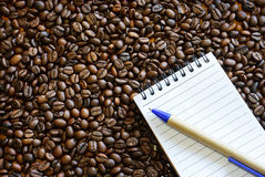 Granos de café y cuaderno Fotografía de archivo libre de regalías