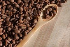 Granos de café y cuchara de madera Foto de archivo libre de regalías