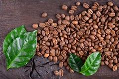 Granos de café y hojas verdes de la planta del café en un escritorio de madera viejo Visión superior Fondo rústico Fotografía de archivo libre de regalías