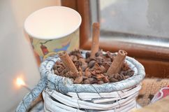 Granos de café y palillos de canela en una cesta de mimbre hermosa imagen de archivo