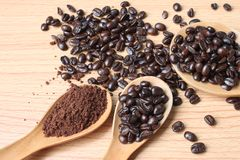 Granos de café y polvo del café en cuchara de madera en una tabla de madera imagenes de archivo