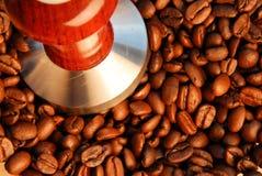 Granos de café y prensa asados del apisonamiento del café express Foto de archivo libre de regalías