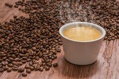Granos de café y taza de café caliente Foto de archivo libre de regalías
