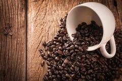 Granos de café y taza de café en la tabla de madera Imagen de archivo