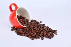 Granos de café y taza roja Foto de archivo