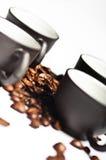 Granos de café y tazas negras Foto de archivo libre de regalías