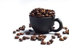 Granos de café y tazas negras Fotos de archivo libres de regalías