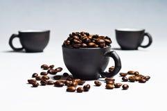 Granos de café y tazas negras Fotografía de archivo
