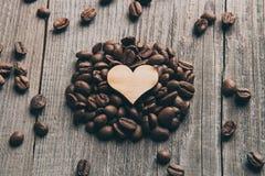 Granos de café y un primer de madera del corazón Imagenes de archivo