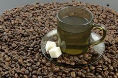 Granos de café y una taza de agua hirvienda Imagenes de archivo
