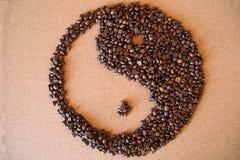 granos de café de Yin-Yang en fondo de madera fotografía de archivo