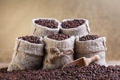 Granos de café asados en pequeños bolsos de arpillera Fotografía de archivo