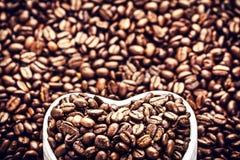 Granos de café asados en un cuenco en forma de corazón en Valentine Day Ho Fotos de archivo