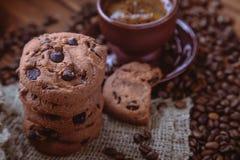 Granos de café asados, galleta con el chocolate y taza en el fondo de madera Imagenes de archivo