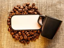 Granos de café con la taza y la etiqueta en blanco en el saco Imágenes de archivo libres de regalías