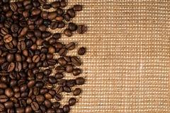 Granos de café dispersados en la arpillera Imagenes de archivo