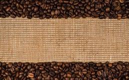 Granos de café dispersados en la arpillera Fotografía de archivo