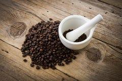 Granos de café en fondo de madera y el mortero blanco Foto de archivo