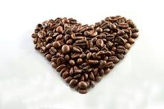 Granos de caf? en fondo del blanco de la forma del coraz?n imagen de archivo