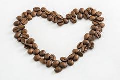 Granos de caf? en la dimensi?n de una variable de un coraz?n foto de archivo libre de regalías