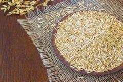 Granos de la avena en una placa de cerámica Puntillas de la avena en una tabla Fotografía de archivo libre de regalías