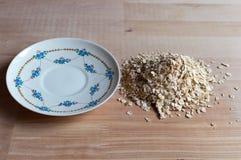Granos de la harina de avena en de madera y la placa cerca Ligh brillante y natural Fotografía de archivo