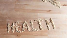 Granos de la harina de avena en la forma de salud de la palabra en el escritorio de madera Brillante y Imagen de archivo