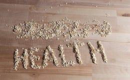 Granos de la harina de avena en la forma de salud de la palabra en el escritorio de madera Parte superior dow Imagen de archivo libre de regalías