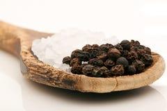 Granos de la sal gruesa y de la pimienta en la cuchara de madera Imagen de archivo libre de regalías