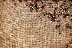 Granos de pimienta sobre lona de la arpillera Foto de archivo libre de regalías