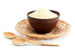 Granos del arroz en un cuenco y una cuchara de madera Imagen de archivo