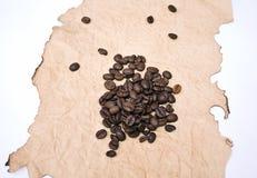 Granos del café en un papel chamuscado Fotos de archivo