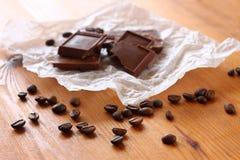 Granos del chocolate, del cinamon y de café en la tabla de madera. foco selectivo. luz natural. Fotos de archivo