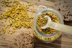 Granos del polen de la abeja en tarro y cuchara de madera en la tabla de madera Apitherapy Productos de la abeja Imagen de archivo libre de regalías