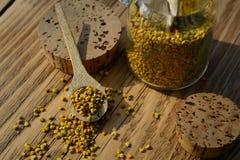 Granos del polen de la abeja en tarro y cuchara de madera en la tabla de madera Apitherapy Productos de la abeja Foto de archivo libre de regalías