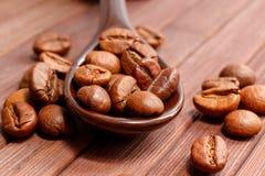 Granos del primer del café Los granos de café están situados en una cuchara a Imágenes de archivo libres de regalías