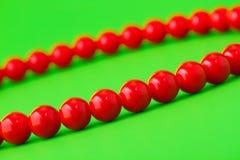 Granos rojos en fondo verde Imagenes de archivo