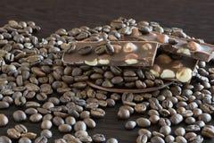 Granos y chocolate de café en un plato y en una tabla de madera Fin-vista imagen de archivo libre de regalías
