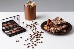 Granos y chocolate decorativos de café de los cosméticos sobre el fondo blanco Foto de archivo