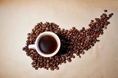 Granos y grano de café, bajo la forma de torbellino y tazas de cristal que mienten en el papel Foto de archivo