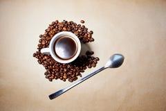 Granos y grano de café, bajo la forma de torbellino y tazas de cristal que mienten en el papel La trayectoria del café de la haba Foto de archivo