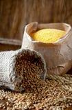 Granos y harina de maíz del trigo en una tabla de madera Imagenes de archivo
