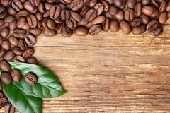 Granos y hoja de café en fondo de madera imagenes de archivo