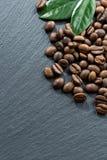 Granos y hojas de café en un fondo oscuro, espacio para el texto imágenes de archivo libres de regalías