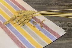 Granos y oídos del trigo en una tabla de madera Foto de archivo libre de regalías